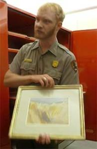 HRC curator holds an original watercolor-and-graphite sketch made by the renowned painter Thomas Moran, whose works were influential in Yellowstone being named America's first national park.