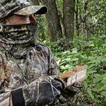 Hunter in woods using turkey box call